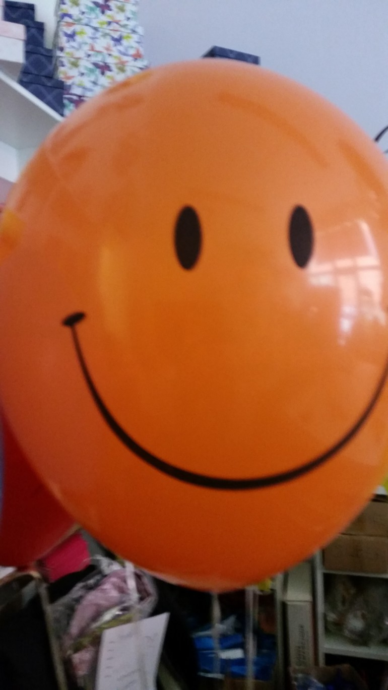 orangefarbener Latexballon Smiley