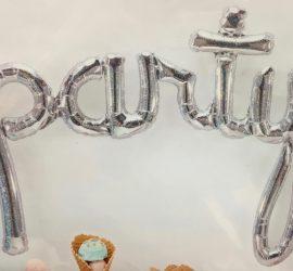 party - Schriftzug in silber - wird mit Luft gefüllt