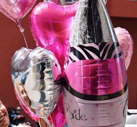 Für den Polterabend: pinkfarbene Champagnerflasche mit Aufschrift Team Bride und pink- und silberfarbene Herzen